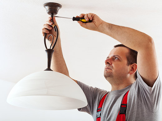 electrician mounting a ceiling lamp